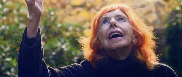 Closeup image of dancer Edith Stephen (95) looking upwards. She is wearing green eyeshadow and has bright orange hair.