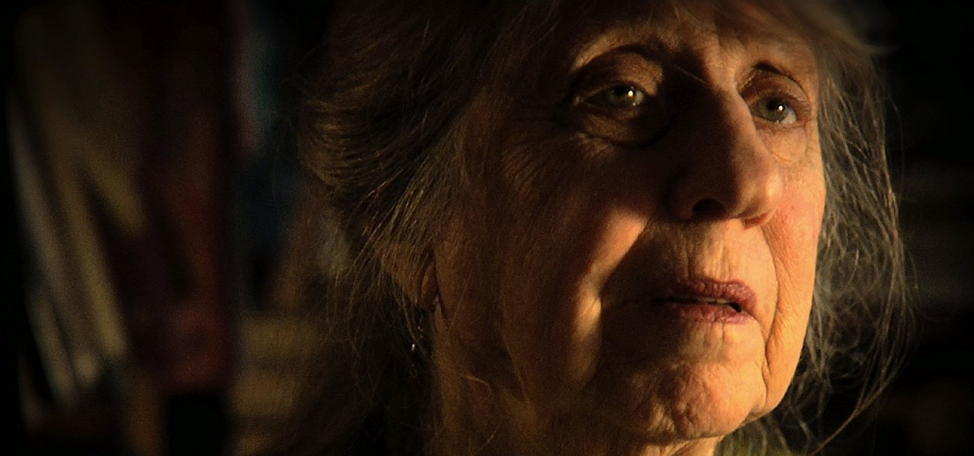 Closeup image of pianist Mimi Stern Wolfe, looking mournfully off into the distance.