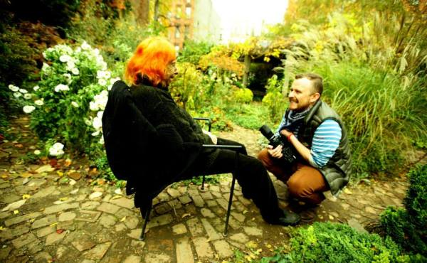 Director Rohan Spong is cradling a large video camera and crouched below dancer Edith Stephen who is seated. They are in a garden on a bright sunny day.